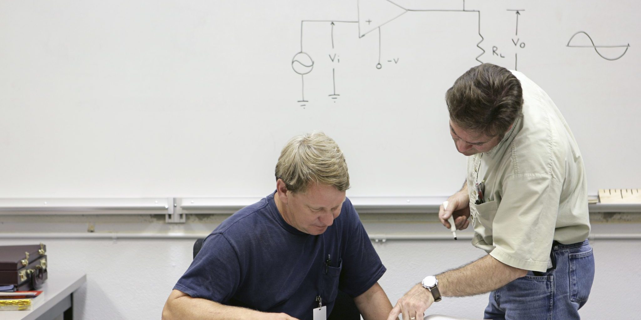 A middle aged adult education student getting help from his teacher.